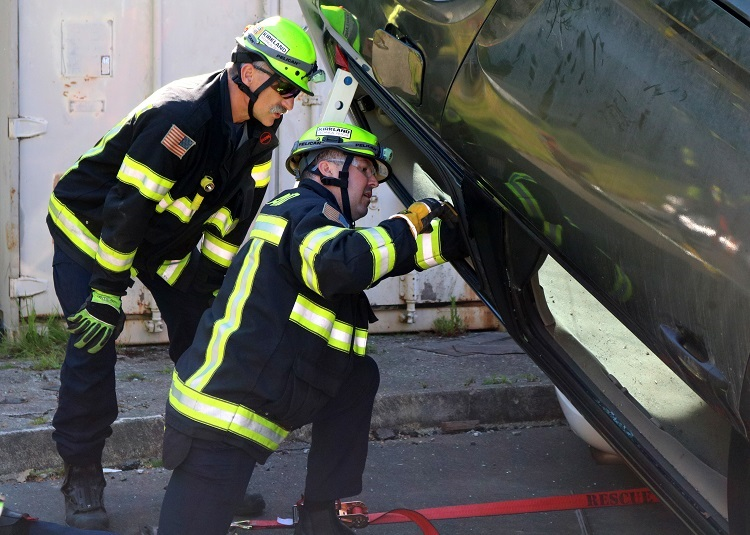Two firefighters looking at an upended vehicle
