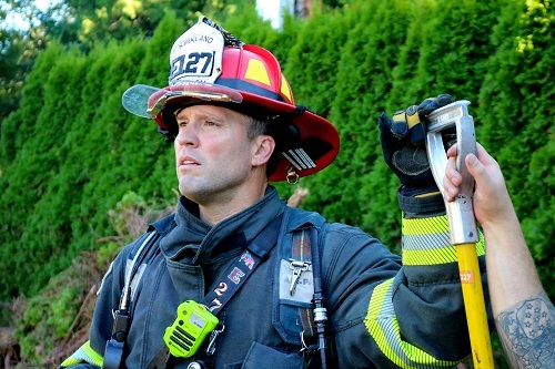 Firefighter in full gear standing outside residence while training