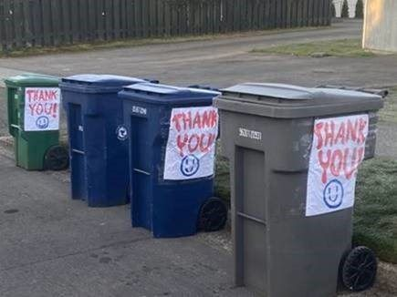 Image of garbage cans with thank you notes taped on them