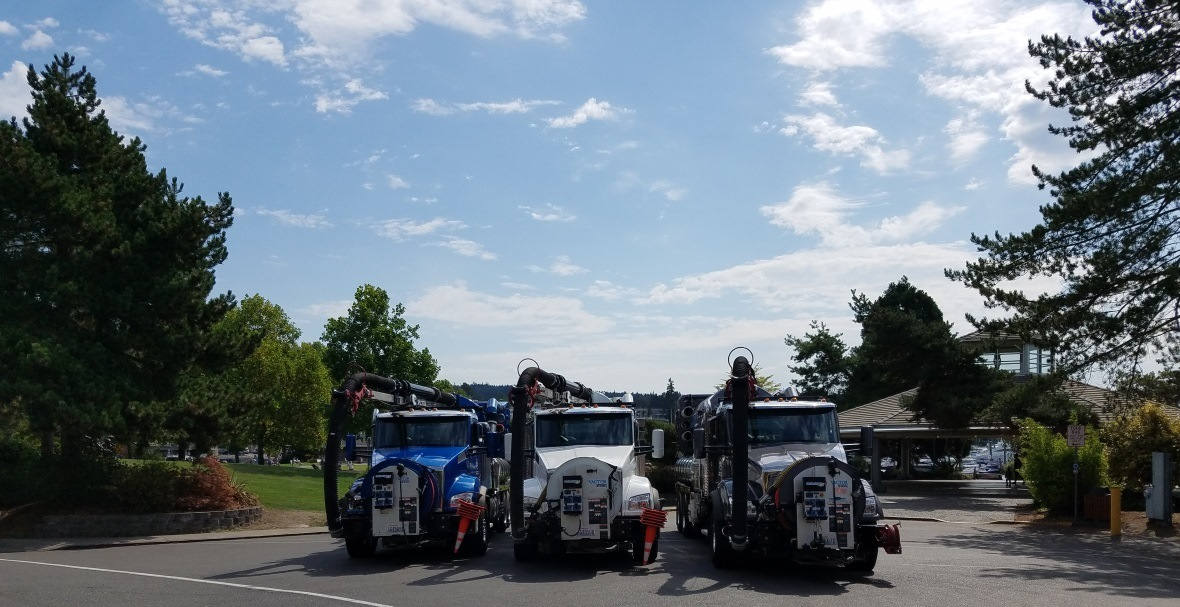 3 vactor tucks lined up in front of Al Lock pavilion at Marina Park.