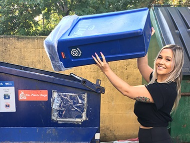 employee at business dumping recycling loose into dumpster