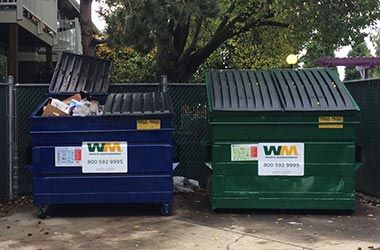 dumpster enclosure at multifamily property showing recycle and garbage dumpsters side by side