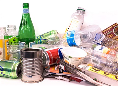 recyclables including glass bottle, plastic bottle, plastic tub, metal cans, and paper
