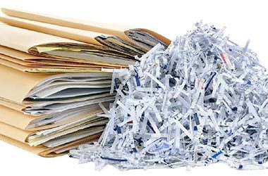 shredded paper with stack of file folders containing paper