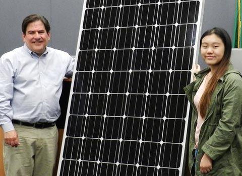 Jay Arnold and resident advocate (young Asian woman with long hair) holding a solar panel that was later installed at City Hall